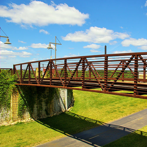A Pony truss bridge locates the deck a bit above the middle of the truss  similar to the through truss, however this type of truss is designed for  lighter